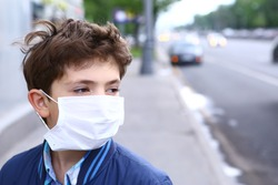 preteen boy in protection mask on the highway city background