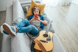 Preteen boy lying with guitar on cozy sofa dressed casual jeans and new sneakers listening to music and chatting using wireless headphones connected with smartphone. Using electronic devices concept