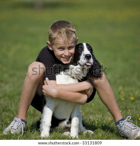 Preteen boy poses in a grass field with his Springer Spaniel puppy.