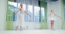Preteen girl and skilled ballerina dance classical ballet by window with curtains in light studio at training lesson