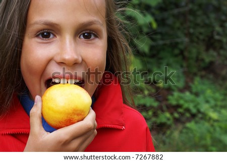 Preteen girl biting a peach on green leaves background - stock photo