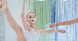 Preteen girl dancer does ballet moves with skilled woman trainer near mirror in spacious light studio at training