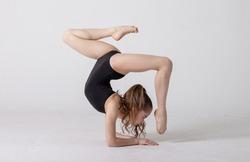 preteen girl gymnast trains on white background in black leotard. children's professional sports. rhythmic gymnastics.