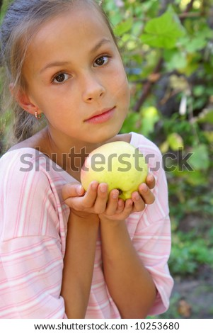 Preteen girl holding a fresh apple - stock photo