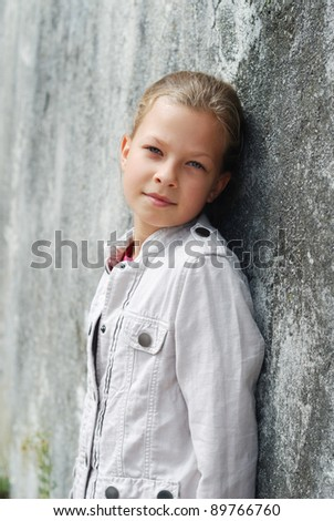 Preteen girl is leaning on the stone wall and looking calmly at the camera.