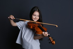 Preteen girl playing violin on black background