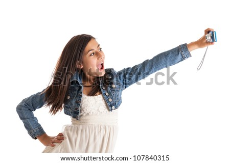 Preteen girl taking a picture of herself with a digital camera isolated on white