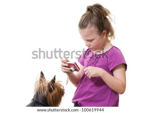 preteen girl taking photo of pet dog