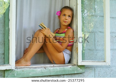 Preteen girl with a book sitting in window - stock photo