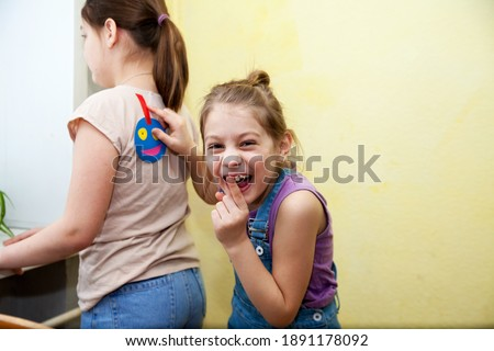 Preteen girl with  face sticker on back against yellow background, space for text. April fool's day Stock photo ©