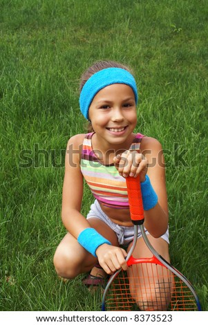 Preteen Girl With Tennis Racket On Grass Background Stock Photo