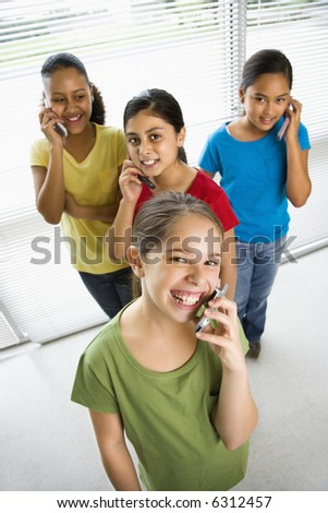 Preteen girls of mutiple ethnicities talking on cell phones and looking at viewer.
