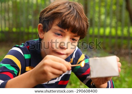 Stock Photo preteen handsome boy play with box of matches
