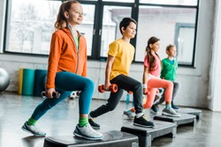 Preteen kids training with dumbbells and step platforms