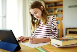 Preteen schoolgirl doing her homework with digital tablet at home. Child using gadgets to study. Education and distance learning for kids. Homeschooling during quarantine. Stay at home entertainment.