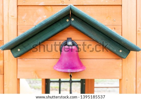Pretend pink school bell on a wooden playground outdoors, with a string for making the ding dong noise, while kids participate in outdoor play. #1395185537
