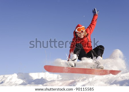 Pretty active young woman in red clothing on snowboard