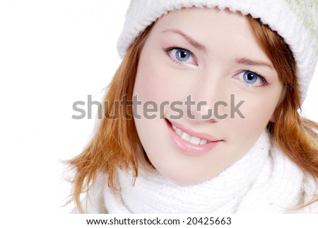Pretty adult girl close-up face in white warm hat looking at camera. Winter concept
