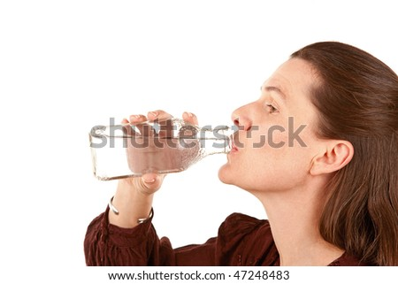 Pretty adult woman drinking water from a glass bottle