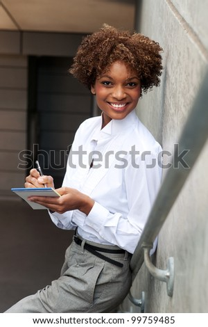 pretty African American executive standing outside with pen and paper