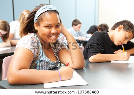 Pretty African-American girl in diverse middle school class.