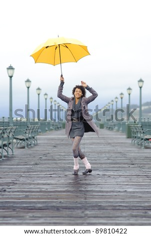 Pretty African American girl with yellow umbrella on the pier