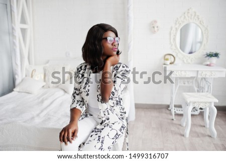 Pretty african american woman in eyeglasses, black and white dress posed in room.