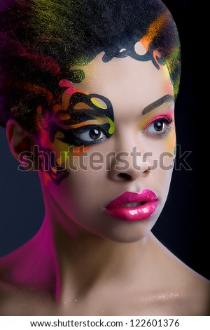 Pretty african girl with neon make up and pink light on dark blue background