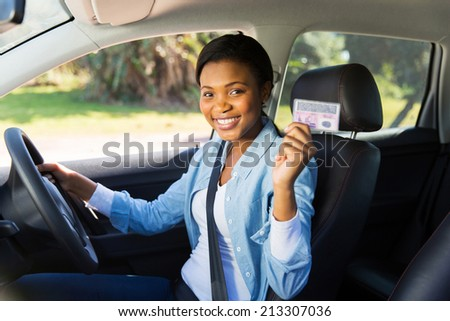 pretty african woman in a car showing her driver\'s license