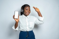 Pretty African woman listening to music, dancing and showing blank phone screen