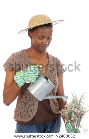 Pretty African woman with watering can and flowers