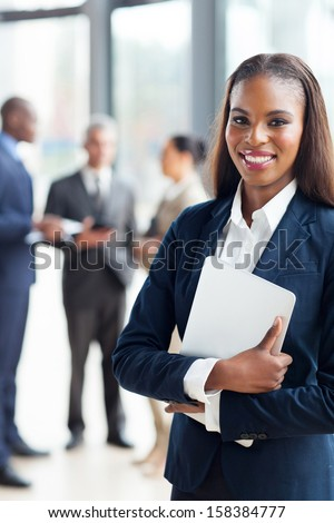 pretty afro american businesswoman holding laptop in office