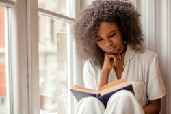Pretty afro-american girl with reading a book sitting on the windowsill.
