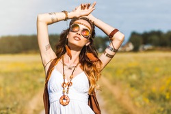 Pretty amazing free red-haired hippie girl dancing outdoors, feathers and braids in her hair, white dress, vest with fringe, accessories, sunglasses, tattoo flash, indie, Bohemian, bo-ho style