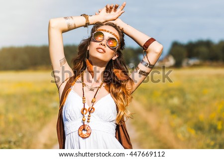 Stock Photo Pretty amazing free red-haired hippie girl dancing outdoors, feathers and braids in her hair, white dress, vest with fringe, accessories, sunglasses, tattoo flash, indie, Bohemian, bo-ho style