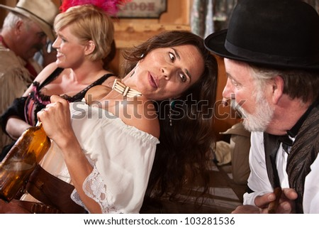 Pretty American Indian gunfighter talking with bartender