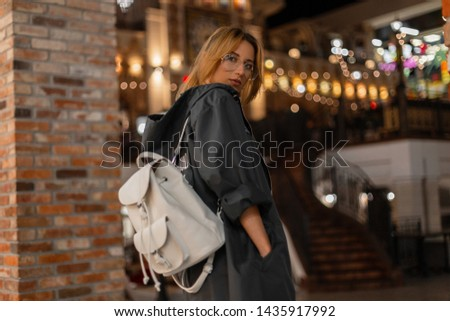 Pretty american young woman hipster in a fashionable jacket with hood in stylish glasses with a stylish white backpack is walks on a shopping center. Pretty girl fashion model enjoys the weekend. Fash
