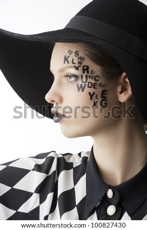 pretty and beautiful young lady with a creative make up made with letter on face and black hat and unusual shirt, she is lightly turned of three quarters at right and looks in to the lens with serious
