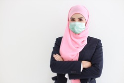 Pretty and confident muslim young asian woman wearing blue suit with medical protective face mask to protect infection from Coronavirus in studio on isolated white background portrait. Covid19 concept