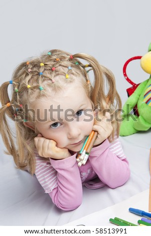 pretty and cute caucasian little girl with extravagant hair tails lying with hands support head and looking appear with pencils batch in grabbed in hands