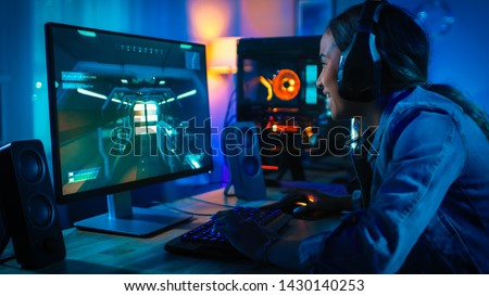Pretty and Excited Black Blogger Girl in Headphones is Playing First-Person Shooter Online Video Game on Her Computer. Room and PC have Colorful Neon Led Lights. Cozy Evening at Home.