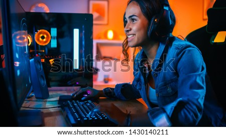 Pretty and Excited Black Gamer Girl in Headphones is Playing First-Person Shooter Online Video Game on Her Computer. Room and PC have Colorful Neon Led Lights. Cozy Evening at Home.