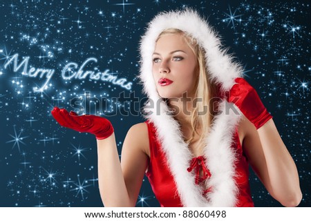 pretty and sensual blond girl in santa claus red dress posing a smiling with a nice hairstyle blowing from hand...