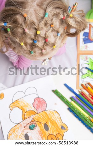 pretty and unique hair tails of young blond caucasian girl thinking and making picture with pencils