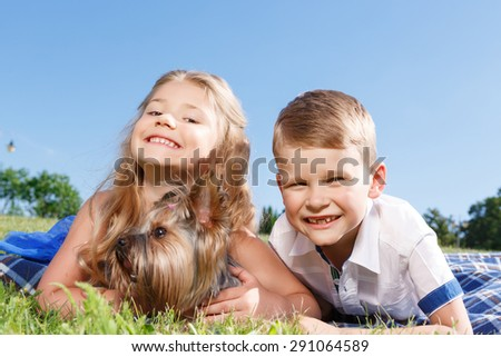 Pretty animal. Positive laughing children holding their hands before them and palming dog while lying on blanket.