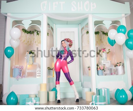 Stock Photo pretty anime girl wearing latex rubber doll catsuit and posing near cute white gift shop with air ballons and presents and gifts for christmas and new year