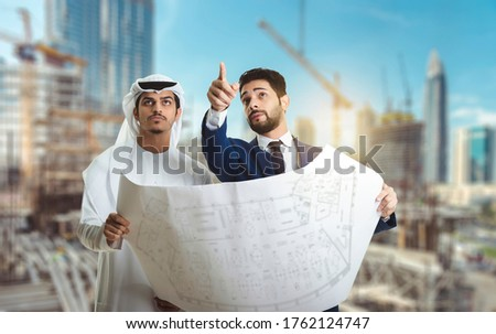 Pretty architect is explaining to Arab builders the plan of construction. The foreman pointing at building with seriousness. Photo stock ©