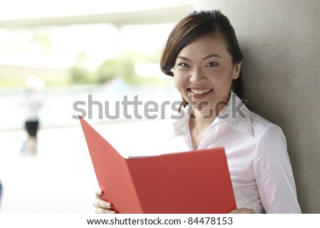 Pretty Asian Business woman holding a Red folder