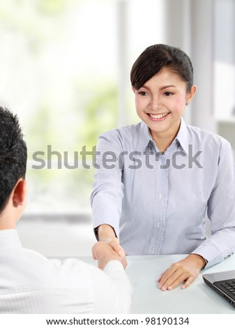 Pretty asian business woman shaking hands with a man in her office