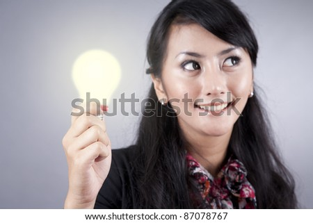 Pretty asian business woman with a light bulb on her hand